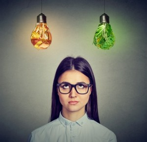 Woman in glasses thinking looking at junk food and green vegetables light bulb isolated on gray background.