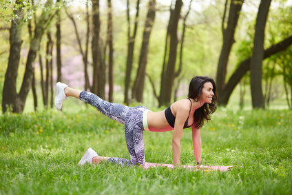 Mature mid age woman practicing yoga outdoors in park. Side view of sporty brunette female working out outside