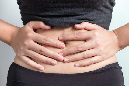 Pregnancy or diet concept, female hands protecting the stomach on white background.