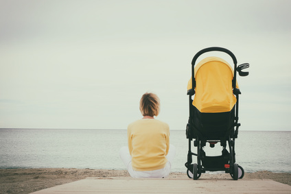 Mother sitting alone next baby stroller on beach by the sea. Cloudy sky with copy space