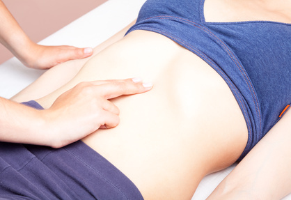 Young woman's abdomen being manipulated by an osteopath - an alternative medicine treatment