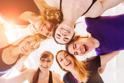 Team of young laughing group of teenager fitness girls hugging together after workout on white background. Underneath view, sun glare effect.